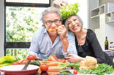 Middle aged couple happy cooking healthy