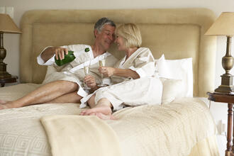 an older couple laying in bed pouring champagne in white robes