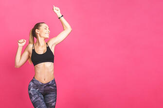 a fit middle aged women jumping in front of a pink background