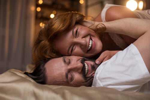 Portrait of happy mature man and woman are having fun in bedroom