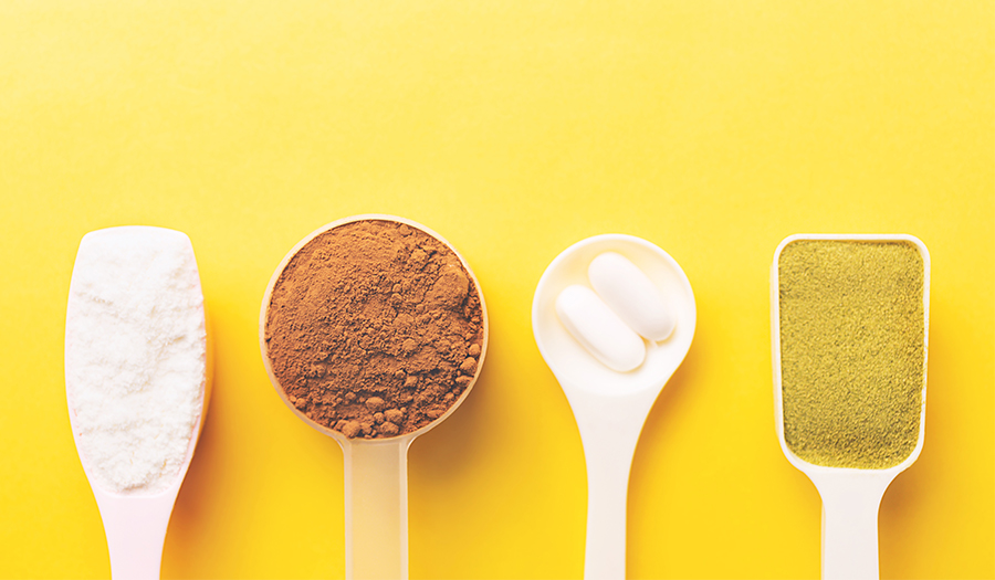 Various collagen powder types on yellow background- plain, matcha, chocolate, pills