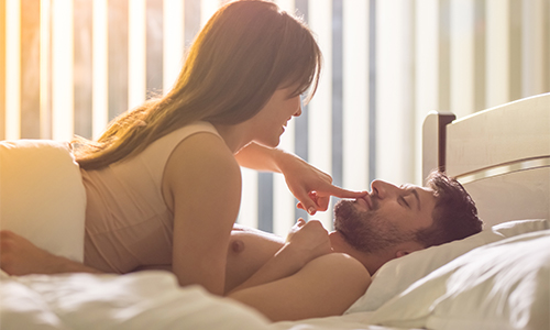 an attractive young couple laying in bed smiling