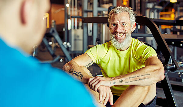 Portrait of a happy middle aged man discussing training results with fitness instructor or personal trainer