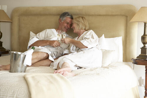 Senior couple at home cuddling in bed