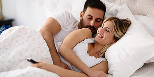 man and woman cudling in bed