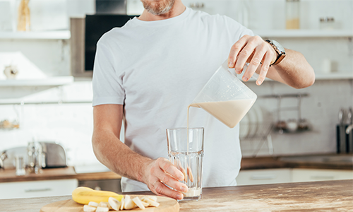 older-man-pouring-banana-protein-shake-at-home