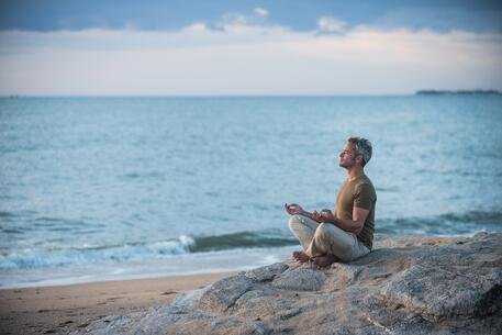 gray-hair-man-yoga-meditation-beach-stress-relief