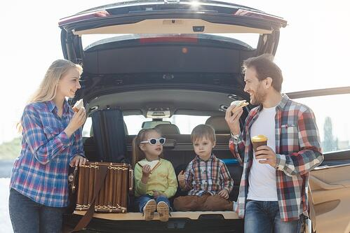 Family eating snacks behind their car