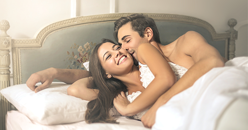 Man and Woman laying down happy in a bed